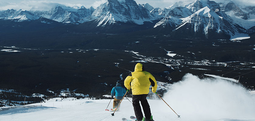 skiers-in-lake-louise-with-mountains.jpg